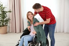 Man covering woman in wheelchair with plaid. Helping disabled stock photo