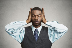 Man covers his ears, eyes closed, hear, see no evil concept. Closeup portrait peaceful, tranquil, relaxed looking, young corporate business man covering his ears Stock Images
