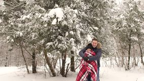 Man covers his girl with a blanket in a snowy park. A man covers his girl with a blanket in the winter snow-covered forest. A romantic couple is walking in the stock video footage