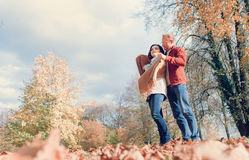 Man covers his wife shoulders with warm shawl in autumn park royalty free stock photo