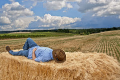 Man with cowboy hat on bale of hay. Man with cowboy hat laying on a bale of hay in a country field stock image