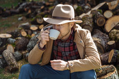 Man cowboy hat drinking morning coffee in countryside Stock Photos