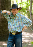 Man with cowboy hat in the forest. Handsome smiling man with cowboy hat in the forest Stock Images