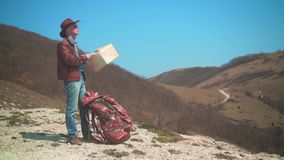 A man in a cowboy hat, leather jacket, blue jeans and glasses is standing in the mountains, considering a traveler map. A man in a cowboy hat, leather jacket stock video footage
