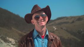 A man in a cowboy hat, leather jacket, glasses. The man looks at the frame and smiles. In the mountains there is a man in a cowboy hat, leather jacket, glasses stock footage