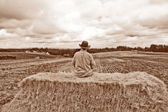 Man with cowboy hat sitting on bale of hay with sepia tone Royalty Free Stock Image