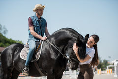 Man in cowboy hat sitting on horseback while woman stroking horse Stock Photography