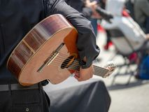Man cradling guitar at a street festival before a performance stock photo