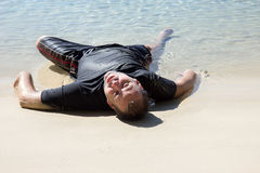 Man crawled out of the sea. Exhausted man crawled out of the sea and lying on the beach Royalty Free Stock Photo
