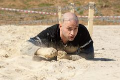 Man crawling on sand stock images