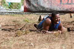 Man Crawls Under Electrified Fence At 5K Obstacle Course Race. Dalton, GA, USA - September 14, 2013: A man smiles triumphantly as he crawls under the last stock images
