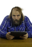 Man with a crazed look in his eyes. What appears to be a frustrated angry man looks up at you from the tablet he is holding in his hands with a crazed look in Stock Image