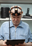 Man crazy inventor wearing a helmet brain research Stock Photography