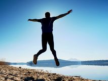Man crazy jumping on beach.  Sportsman flying on beach during the sunrise above horizon Royalty Free Stock Image