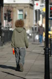 A man with a crazy red afro. Haircut walking down the street Stock Photography