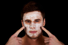 Man with cream moisturizer on his face. Royalty Free Stock Photography