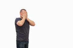 The man creates an image gestures and a mimicry. The man creates an image of grief having shut the face with the hands, on the isolated background Royalty Free Stock Photo