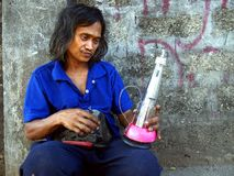 A man creates and sells an alcohol fueled lamp made out of recycled materials. ANTIPOLO CITY, PHILIPPINES - APRIL 24, 2017: A man creates and sells an alcohol stock photo