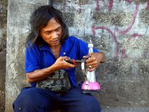 A man creates and sells an alcohol fueled lamp made out of recycled materials. ANTIPOLO CITY, PHILIPPINES - APRIL 24, 2017: A man creates and sells an alcohol stock photography