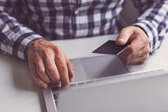 Man with credit card in hand and laptop Stock Image