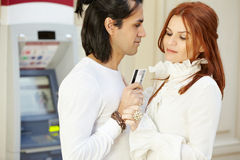 Man with credit card in hand and woman. Dark-haired men with credit card in hand and red-haired women stand face to face, she holds his hand and looks at card Royalty Free Stock Photos