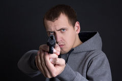 Man criminal aiming with gun over grey Stock Photography