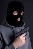 Man criminal in black mask with gun over grey Royalty Free Stock Images