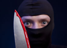 Man criminal in black mask with knife Stock Photos