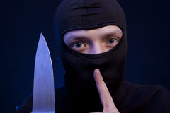 Man criminal in black mask with knife Royalty Free Stock Photos