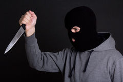Man criminal in black mask with knife over grey Stock Photo