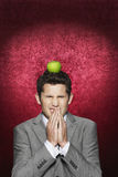 Man Cringing With Apple On His Head. Young man cringing with apple on his head against red velvet background stock photography