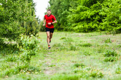 Man cross country running on trail stock photo