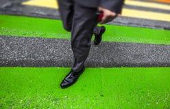Man cross street at crosswalk in the city Stock Images