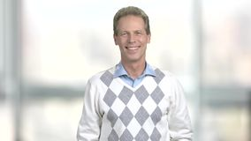 Man crossed arms o blurred background. Middle-aged man folded his arms on office background. Cheerful office manager stock video
