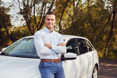 Man with crossed arms stands in front of his new car royalty free stock photography