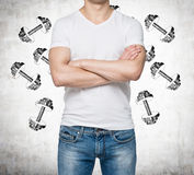A man with crossed hands is pondering about weights. Stock Image