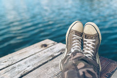 Man with crossed legs relaxing on riverbank pier. Casual young guy wearing sneakers sitting by the river in summer afternoon, selective focus Royalty Free Stock Images