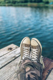 Man with crossed legs relaxing on riverbank pier. Casual young guy wearing sneakers sitting by the river in summer afternoon, selective focus Stock Photos