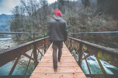 Man crosses an iron and wooden footbridge on the river Royalty Free Stock Images