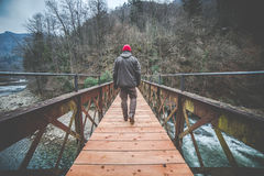 Man crosses an iron and wooden footbridge  wood on the river Royalty Free Stock Photo