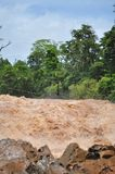 Man crosses the Khone Phapheng falls on the Mekong River in Laos on a rope during the Monsoon flooding royalty free stock images