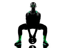 Man crossfit  weight disk exercises fitness silhouette. One man exercising weight disk fitness crossfit  in silhouette isolated on white background Stock Photo