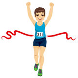 Man Crossing Finish Line. Male runner crossing red finish line and celebrating victory with fists up Royalty Free Stock Image