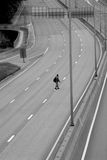 Man crossing the motorway. Man walking across an empty motorway. Black and white photo Royalty Free Stock Photo