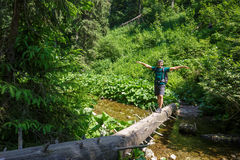 Man crossing a mountain river. Happy male hiker crossing a mountain river on a huge tree trunk Stock Photo
