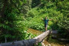 Man crossing a mountain river Stock Photo