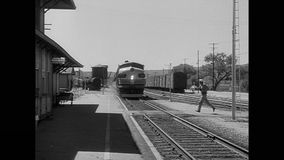 Man crossing railroad tracks in front of train stock video