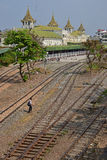 A man is crossing the railway tracks behind Yangon Central Railway Station Royalty Free Stock Photography