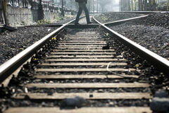 Man crossing railway tracks Stock Photography