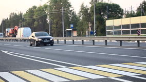 A man crossing the road at the crosswalk. A man crossing the highway at the crosswalk stock video